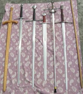 From Left to Right: Wooden Longsword 'Waster' from Purpleheart Armouries; Angus Trim AT1548 Longsword; Pavel Moc 'Embleton' Longsword; Angus Trim 'AT1431' Arming Sword; Darkwood Armouries '2 Ring Economy Hilt' Rapier; Pavel Moc 'Durer' Longsword; Basic Mk1 wooden stick